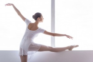 Training her flexibility. Rear view of beautiful young ballerina doing stretching exercises in ballet studio